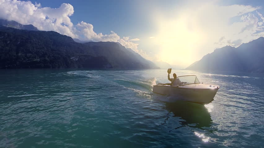 happiness lifestyle background. young man enjoying boat ride on lake. aerial view fly over