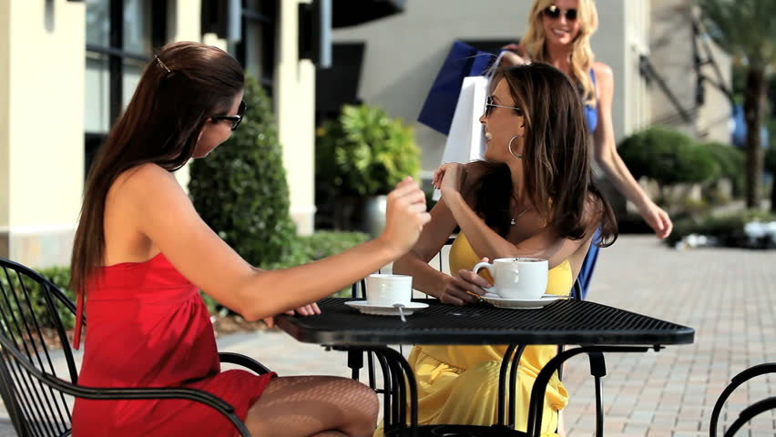 Three sophisticated female friends meeting at outdoor cafe after a successful shopping trip - HD stock video clip