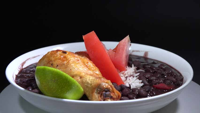 Traditional Cuban meal from the Cuban Cuisine: white rice and soup of black beans plus fried chicken and ripe tomatoes salas. Dish turning in restaurnat exhibitor or display.