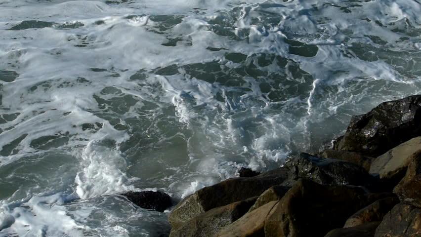 An ocean wave breaks against the rocks in slow motion.