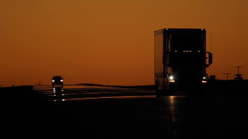 Dawn traffic with orange sky. Semi truck approaches and passes, with pickup truck in the distance. Saskatchewan, Canada.