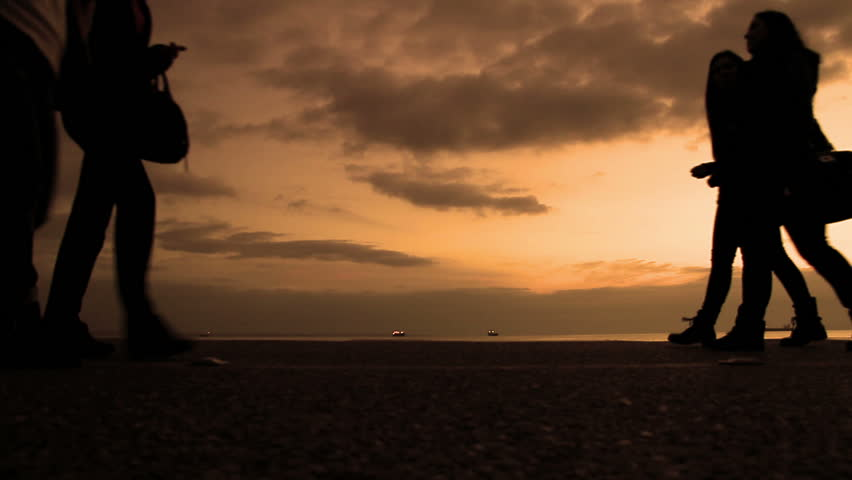 Silhouettes of People Walking at Port near Sea, Against Dramatic Sky of Sunset - Orange tone version - Full high Definition video 1920X1080 - HD stock footage clip