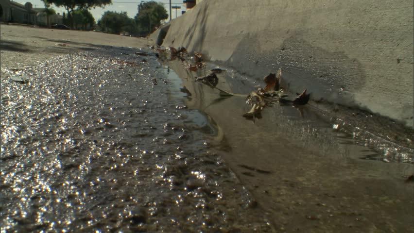 Water draining down a street curb. - HD stock video clip