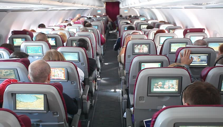 Passengers sit in chairs during the flight of the aircraft Qatar Airways.Inside view of the interior of the aircraft. Russia, Moscow,March,15,2014
