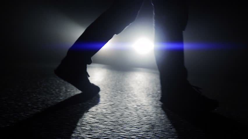 foot steps of man walking at night. car light beams. mystery scene background