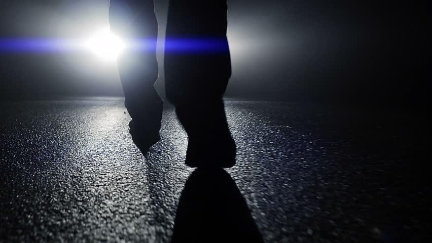 camera following feet walking towards car light beams in dark night. foot steps close up