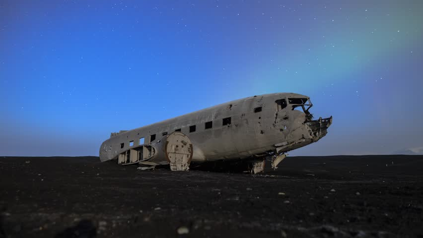 Plane wreck at Solheimasandur, Iceland with glow of aurora, or northern lights, in the sky. The plane was forced to land here on Nov 24, 1973. Timelapse footage by moonlight.