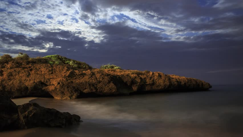 Moonrise over the Mediterranean Sea at castle Tamarit, with clouds.  Timelapse footage.