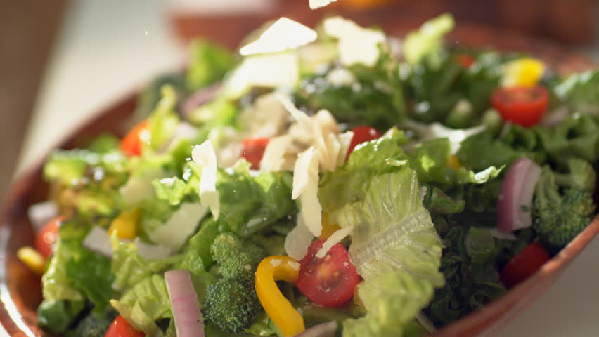 Camera follows parmesan cheese being put on salad. Shot with high speed camera, phantom flex 4K. 4K 30fps. Slow Motion.
