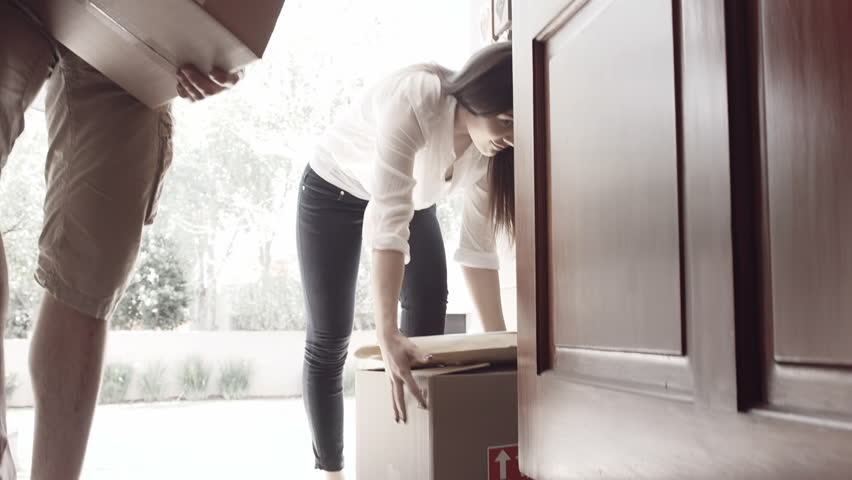 Young couple picking up moving boxes and walking through their door of new apartment while moving in.  | Shutterstock HD Video #7817866