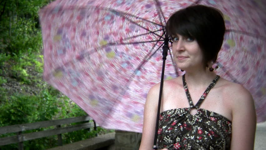 Attractive woman smiles and spins her umbrella - HD stock video clip