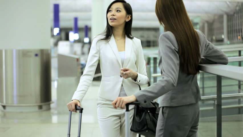 Business colleagues consultants female American Asian Chinese suit airport departures travel destination professional meeting airline passengers | Shutterstock HD Video #7876159