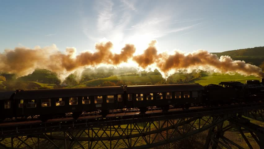 epic aerial view of steam engine train crossing bridge at sunset magic hour. old locomotive - 4K stock footage clip