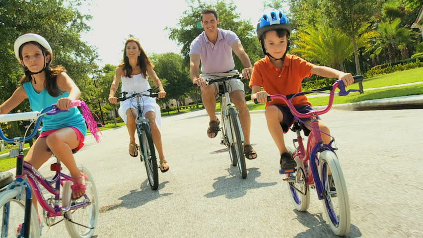Attractive healthy caucasian family enjoying keeping fit together cycling outdoors 60FPS - HD stock video clip