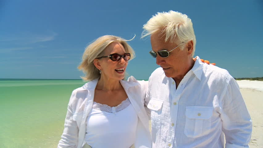 Attractive senior couple enjoying each others company walking on the beach 60FPS - HD stock footage clip