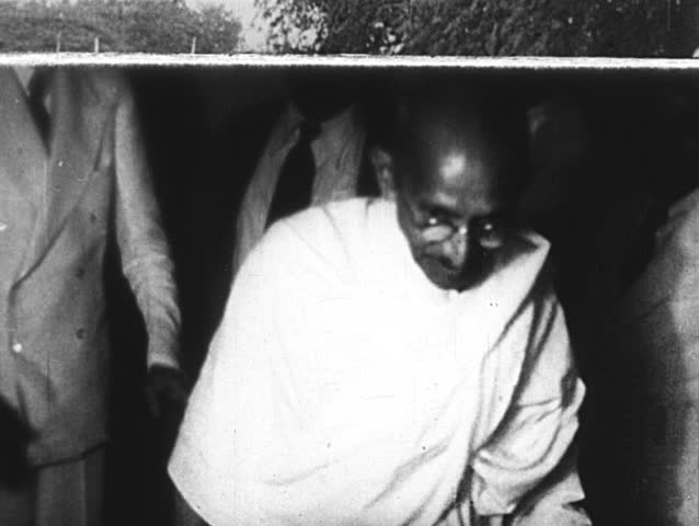 INDIA- CIRCA 1930: Gandhi speaks to smiling reporters. Gandhi stands with his hands pressed together in prayer, places his finger over his lips to shush a crowd, then takes a seat on a pillow