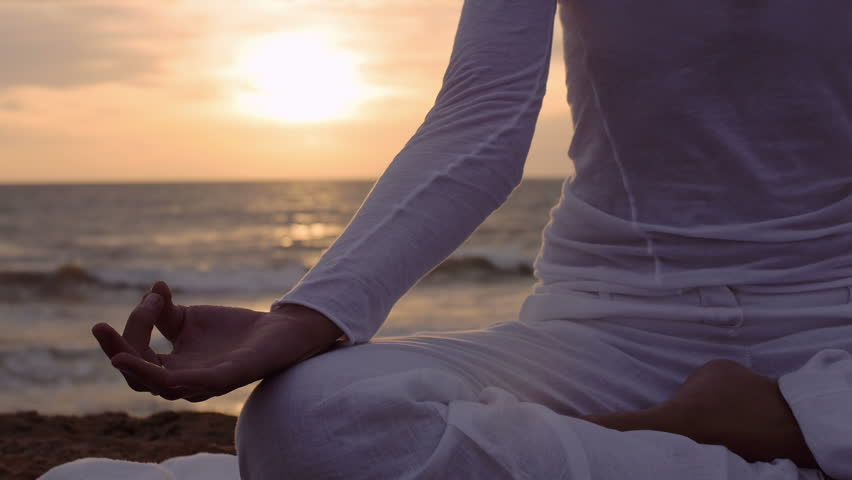 particular on hand of a woman in meditation on the beach: yoga position