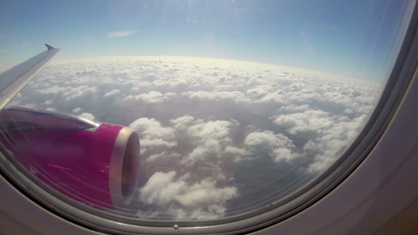 Aircraft flying near clouds sunny flight, wing turbine blue sky