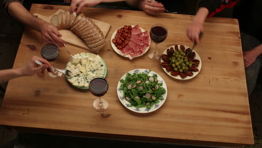 Preparing and eating food on wooden table with friends (antipasto, bread, salad, ham, cheese, olives, dried tomatoes...), 4K, top view - 4K stock footage clip