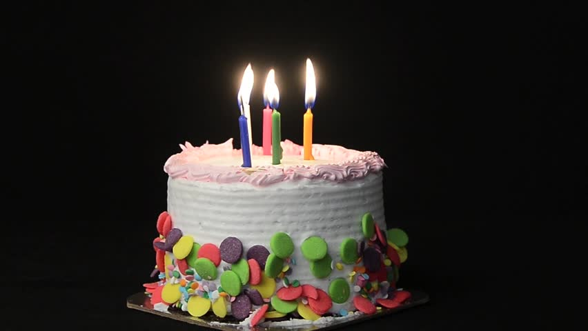 Candles burning on top of a birthday cake/Happy Birthday/Candles are burning and are blown out