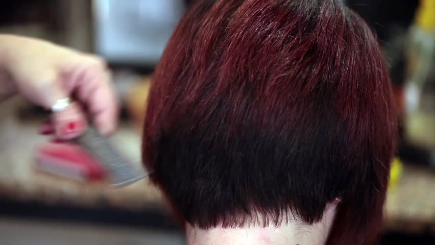 Video of young woman getting a new haircut by hairdresser, closeup shot.