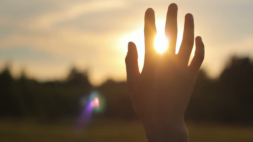 Close-up of raised hand in the sky against the sun in nature, religion, spirituality, camera movement