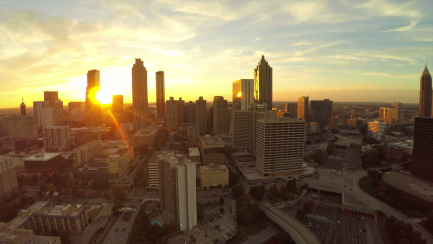 Atlanta aerial flying backwards with cityscape sunset view.
