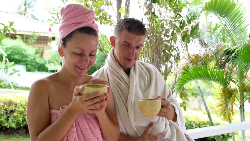 Attractive Young Couple Are Drinking Hot Coffee after Shower in Towels Outdoors in the Terrace of their House. HD, 1920x1080. - HD stock video clip