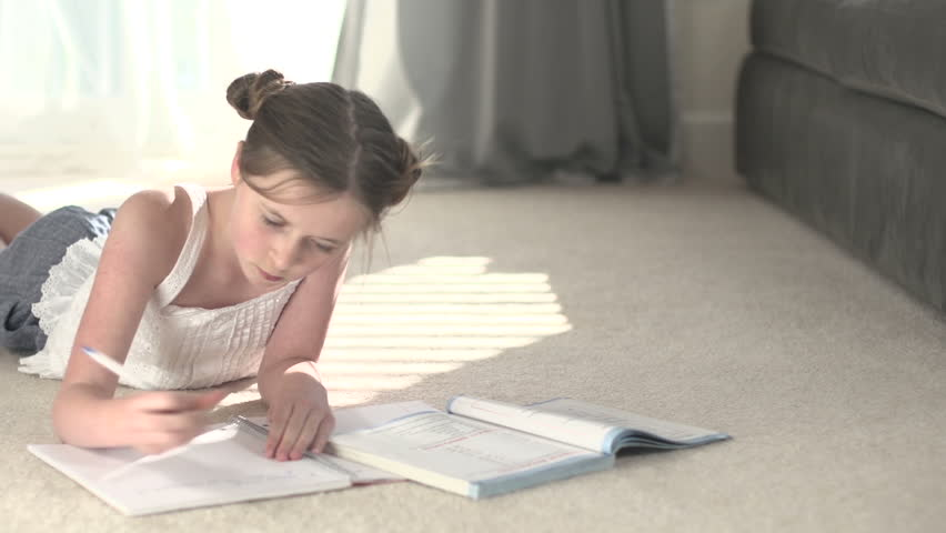 A pan left to a young girl lying on her stomach on the carpet, writing notes from a book. She looks up and smiles to camera. | Shutterstock HD Video #7971919