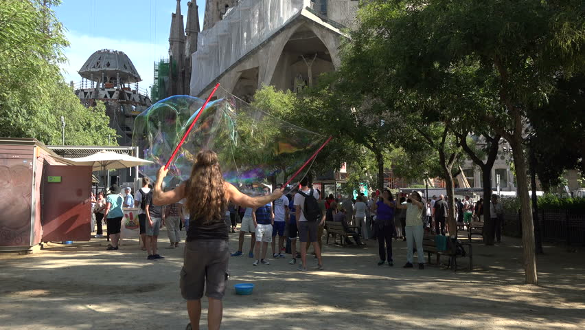 BARCELONA, SPAIN - SEPT 2014: Barcelona Spain soap bubble fun Sagrada Familia. Visitors, tourists, locals walking and traffic in front of church. Construction began in 1882 and is over 50% completed. - 4K stock video clip