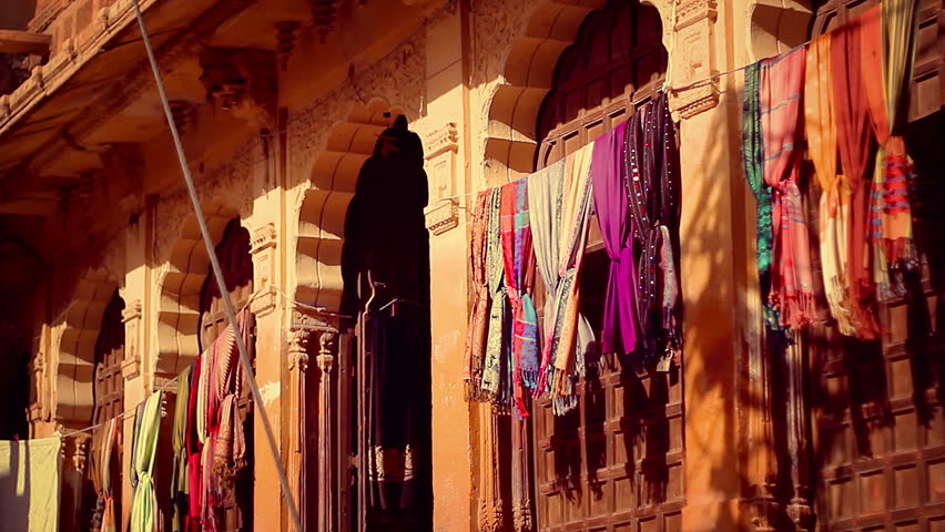 An Haveli entrance on Jaisalmer Fort, with elaborately sculpted sandstone columns, and colorful pashminas shawls swaying with the wind. Golden sunset light on a locked down camera shot. | Shutterstock HD Video #7989199