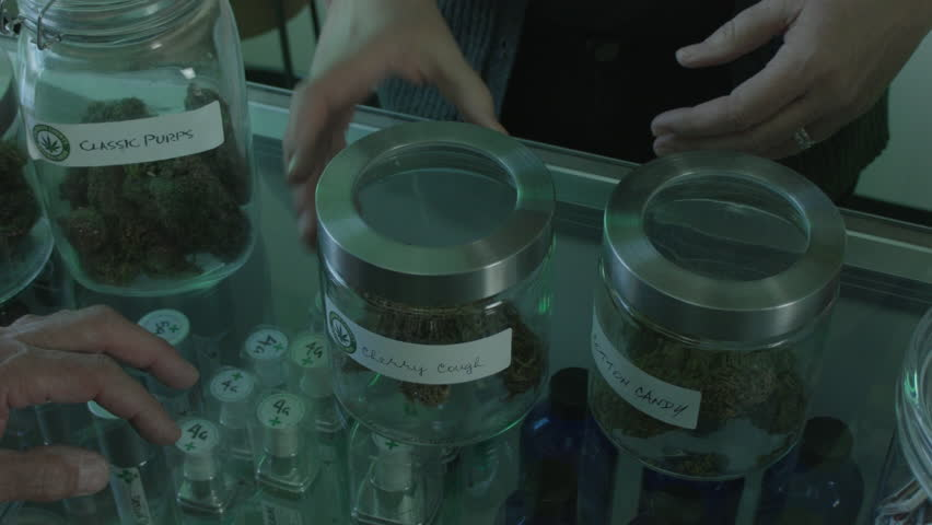 """MEDICAL MARIJUANA DISPENSARY CUSTOMER'S P.O.V. AS AN EMPLOYEE HANDS HIM SOME PRODUCT FOR INSPECTION. CUSTOMER SMELLS THE PRODUCT. LABEL ARTWORK CREATED & CLEARED BY """"PROP HEAVEN"""" IN BURBANK, CALIF."""