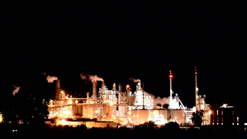 Night view of a chemical industrial plant along a city street with passing cars and trucks. - HD stock video clip