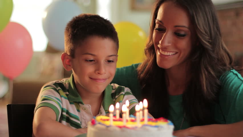 Mother and son blowing out the candles on a birthday cake together - HD stock video clip