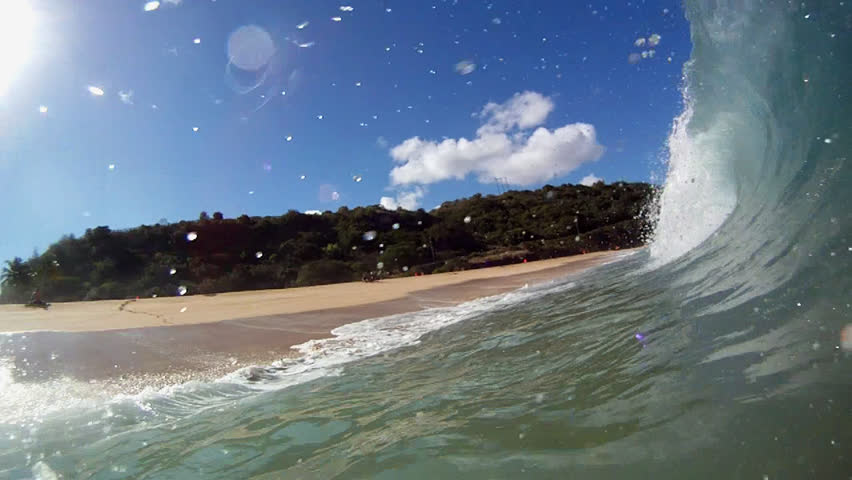 4 Shots of waves breaking over the camera on the beach in Hawaii.