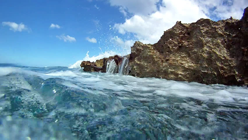 A wave crashes against the rocks and then splashes the camera.