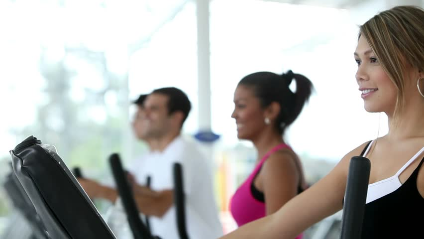 people at the gym exercising on a cross trainer  - HD stock footage clip