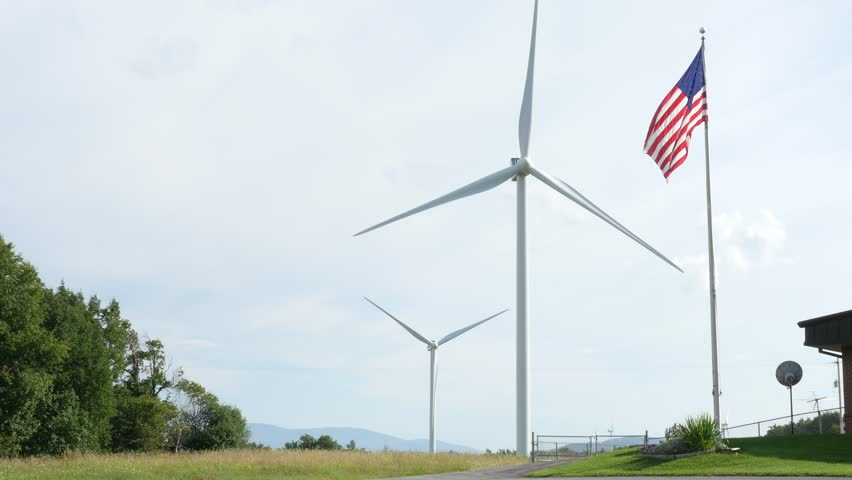 Wind Turbines In New York State Generating Clean Renewable Electricity, With The American Flag Flying In The Foreground