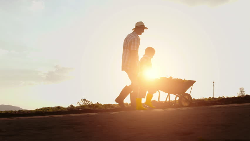 Farming father helping son push wheelbarrow up hill on their farm at sunset.