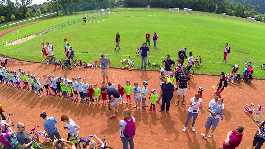 VRHNIKA, SLOVENIA - AUGUST 2014: Kids standing in line and waving to flying camera. Youngsters waiting for reward for finishing bicycle competition. - HD stock video clip