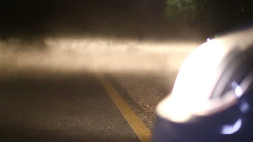Car headlights in dust switched on.