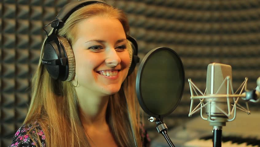 The teen girl sings at the professional audio studio. Portrait view