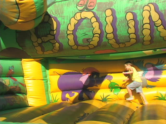 A SMALL BOY HAS FUN ON A BOUNCE RIDE AT AN AGRICULTURAL FAIR. - SD stock video clip