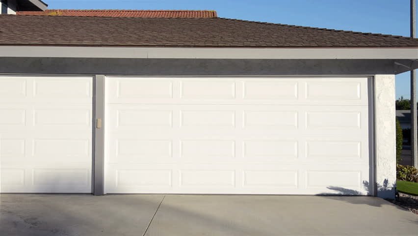 A residential home with an automatic roll up garage door moving in the opening position.