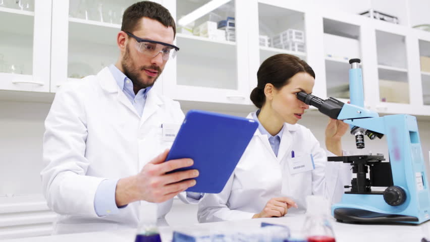 Scientists In Lab Work With Microscope And Computer Stock