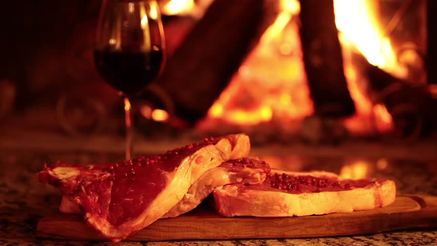 Video clip of raw beef steaks in front of the fireplace expressing a concept of traditional healthy country lifestyle.