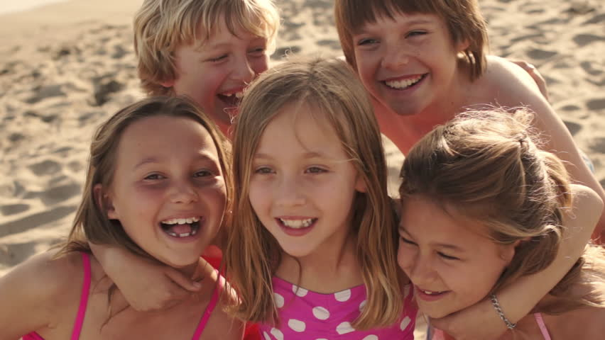 Close Up Of Five Children On Beach Facing Camera And Laughing. - HD stock video clip