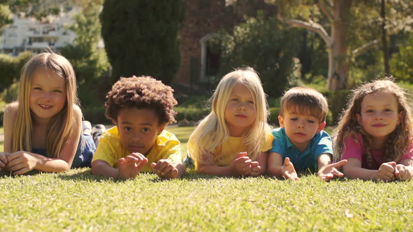 Five Children Lying On Grass In Park Looking At Camera. - HD stock footage clip