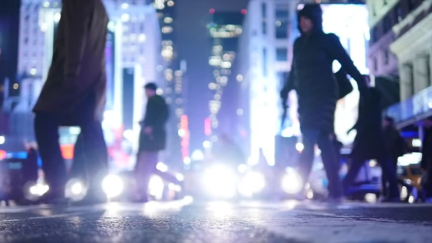pedestrians crossing crosswalk in city at night. new york city street background