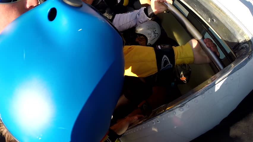 A group of skydivers jump together from a plane before gliding in the air over a landscape, POV - HD stock video clip